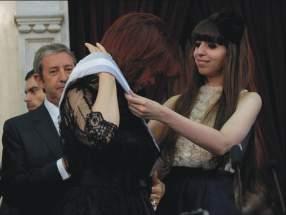 Tras jurar, Cristina tomó la banda y se la dio a su hija Florencia quien le ayudó a colocársela